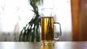 A cerveja é derramada à caneca meio vazia na tabela video estoque