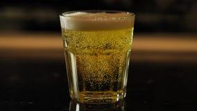 A cerveja é derramada em um vidro vídeos de arquivo