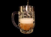 A cerveja é derramada em uma caneca Imagens de Stock