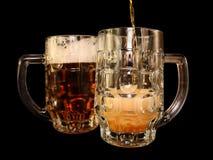 A cerveja é derramada em uma caneca Fotos de Stock