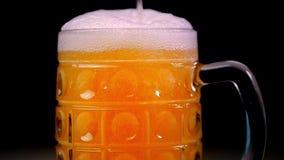 A cerveja é derramada no vidro em um fundo preto A espuma desliza rapidamente através do vidro Grande espuma extrema da cerveja e filme