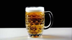 A cerveja é derramada no vidro em um fundo preto A espuma desliza rapidamente através do vidro Grande espuma extrema da cerveja e vídeos de arquivo