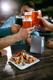 Cerveja bebendo Amigos que aumentam vidros da cerveja Fotografia de Stock Royalty Free