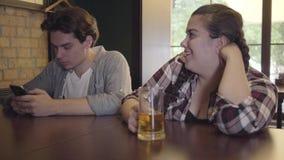 Cerveja bebendo da menina gorda com os amigos que sentam-se na tabela na barra Homem novo que texting em seu telefone celular qua filme