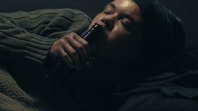 Cerveja bebendo do homem desabrigado, encontrando-se na sujeira, apego de álcool na pobreza impossível video estoque