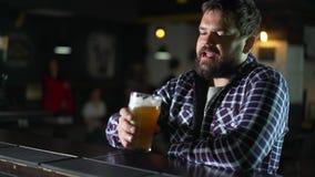 Cerveja bebendo do homem farpado e apreciação de uma bebida na barra do bar O convidado masculino tenta um vidro da cerveja filme