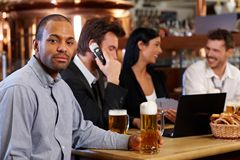 Cerveja bebendo do homem novo no bar Fotos de Stock Royalty Free