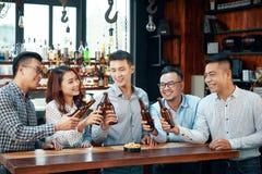 Cerveja bebendo dos povos satisfeitos na barra fotografia de stock royalty free