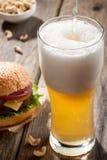 Cerveja clara com um hamburguer e os petiscos Fotografia de Stock Royalty Free