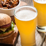 Cerveja clara com um hamburguer e os petiscos Foto de Stock Royalty Free