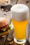 Cerveja clara com um hamburguer e os petiscos Foto de Stock