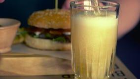 Cerveja clara de derramamento no vidro Um Hamburger com legumes frescos e vidros de cerveja filme