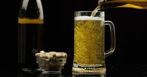Cerveja clara fria de derramamento da garrafa em um vidro Close-up da cerveja do of?cio video estoque