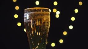 A cerveja clara fria em um vidro com água deixa cair sobre o fundo preto matte com luz borrada video estoque