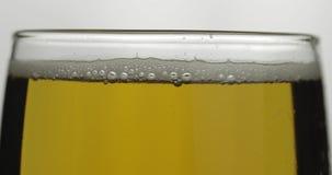 Cerveja clara fria em um vidro Macro do close-up da cerveja do of?cio Rota??o 360 graus filme