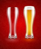 A cerveja com espuma no vidro e esvazia o cálice transparente para beber Foto de Stock