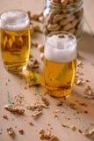 Cerveja com os amendoins na tabela de madeira velha Imagem de Stock
