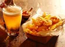 Cerveja com peixes e batatas fritas fritados Imagens de Stock