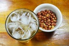 A cerveja come pares com o amendoim de sal no copo Fotos de Stock