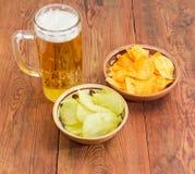Cerveja de cerveja pilsen e vária microplaqueta de batata dois em umas bacias cerâmicas Fotos de Stock