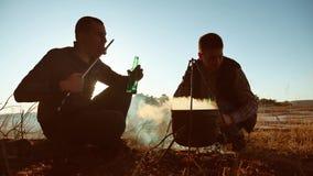 A cerveja de dois turistas está sentando o estilo de vida pelo partido da fogueira no por do sol de acampamento da luz solar da s vídeos de arquivo