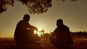 A cerveja de dois turistas está sentando o estilo de vida pelo partido da fogueira no por do sol de acampamento da luz solar da s video estoque