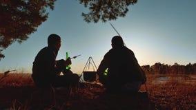 A cerveja de dois turistas está sentando o estilo de vida pelo partido da fogueira no por do sol de acampamento da luz solar da s filme
