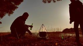 A cerveja de dois turistas está sentando-se pela fogueira que caminha o partido no estilo de vida de acampamento do por do sol da filme