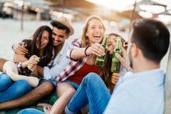 Cerveja de sorriso e bebendo dos pares felizes na praia fotos de stock