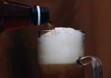A cerveja derramou em um vidro com uma espuma agradável Foto de Stock Royalty Free