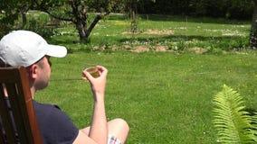 Cerveja do álcool da bebida do homem no jardim Vista traseira 4K filme