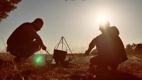 A cerveja do estilo de vida de dois turistas está sentando-se pela fogueira que caminha o partido no por do sol de acampamento da filme