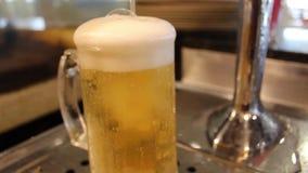 A cerveja do ofício derramou em um vidro da pinta Cerveja de derramamento do barman da torneira no vidro na barra, close up filme
