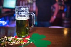 Cerveja e amendoins verdes em um contador Fotografia de Stock Royalty Free