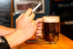 Cerveja e cigarro Fotos de Stock Royalty Free