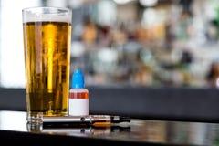 Cerveja, e-líquido e atomizador na barra fotos de stock