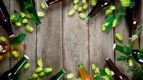 Cerveja e lúpulos verdes Na tabela de madeira Fotografia de Stock