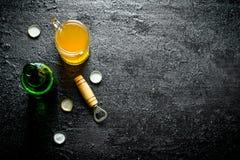 Cerveja em um vidro e em uma garrafa de vidro aberta com abridor fotos de stock