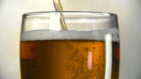 A cerveja escura é derramada em um vidro Movimento lento das bolhas na cerveja filme