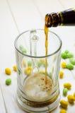 Cerveja escura que derrama em um vidro fotografia de stock