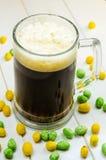 Cerveja escura que derrama em um vidro imagens de stock