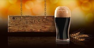 Cerveja escura, trigo e placa de madeira imagem de stock