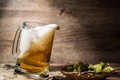 A cerveja espumoso derramou da caneca que está no pano de linho Imagens de Stock
