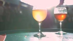 A cerveja está derramando da parte superior no vidro vídeos de arquivo