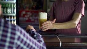 A cerveja está derramando da parte superior no vidro que forma ondas filme