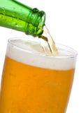 A cerveja está derramando no vidro Imagens de Stock