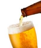 A cerveja está derramando no vidro Foto de Stock
