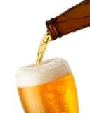 A cerveja está derramando no vidro Imagem de Stock