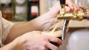 A cerveja está derramando no vidro angular A cerveja de malte, luz, cerveja não filtrada, apronta-se para beber a cerveja filme