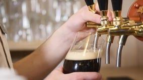 A cerveja está derramando no vidro angular A cerveja de malte, luz, cerveja não filtrada, apronta-se para beber a cerveja video estoque